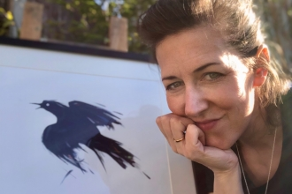 Portrait of Lucia Hardy with bird art work behind her