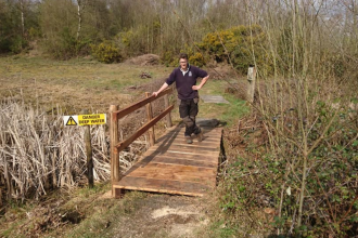 Ranger Alex, standing on a bridge on the reserve